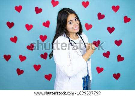 Young doctor woman wearing medical coat and stethoscope over blue background with red hearts feeling happy, positive and successful, motivated when facing a challenge or celebrating good results