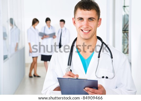 Young doctors are standing intside the hospital and looking at camera