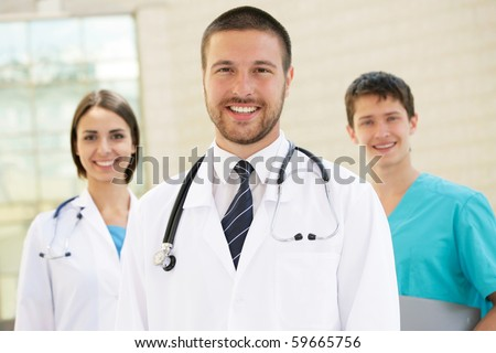 Young doctors stand against a hospital building