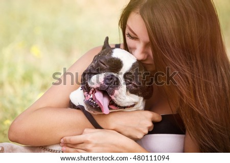 Young dog owner girl plays with french bulldog puppy in park outdoor.Teen brunette female kissing little puppy.Domestic canine breed.Young woman cuddling her pet doggy