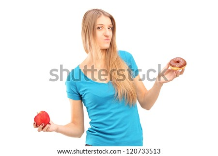 Young doubtful female holding a red apple and donut trying to decide which one to eat - stock photo