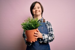 Young down syndrome gardener woman wearing worker apron holding green plant pot with a happy face standing and smiling with a confident smile showing teeth