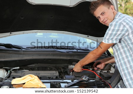 Young driver uses battery jumper cables to charge dead battery #152139542