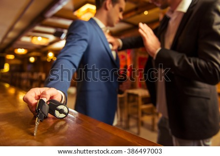 Young drunk businessman is holding a bottle of beer and reaching car keys on bar counter in pub, another man is stopping him #386497003