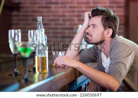 Young drunk man drinking alcohol in the bar