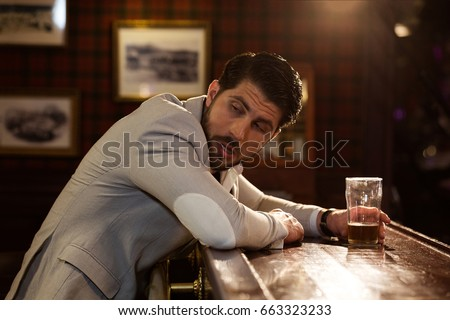 Young drunk man sitting at the counter in a pub or a bar and drinking beer #663323233