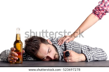Young drunk man with car key and bottle of beer on grey background #523697278