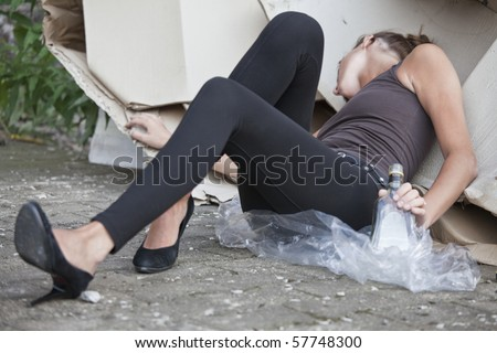 young drunk woman with bottle in her hand sleeping outdoor