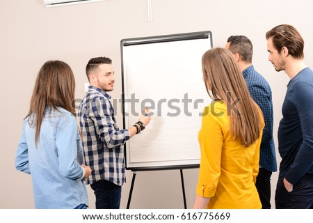 young dynamic business team man and woman discussing around a flip chart white board in meeting room #616775669