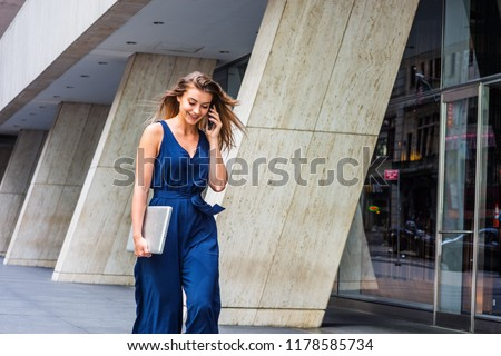Young Eastern European American Woman talking on cell phone, traveling, working in New York City, wearing blue sleeveless jumpsuit, carrying laptop computer, walking on street outside office building. stock photo