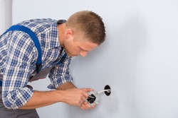 Young Electrician Installing Electrical Socket On Wall In House