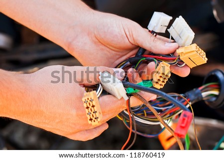 Young electrician man holds the wires