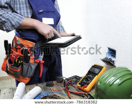 Young electrician working with laptop in a residential electric installation