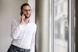 Young elegant bearded serious man leaning on the pillar indoors and having phone conversation.