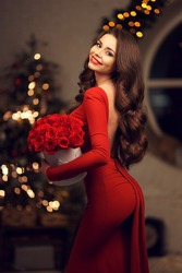 Young elegant beautiful lady in red dress with bouquet of red roses posing in evening interior