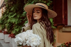 Young elegant brunette woman with long waved hair wearing wide brim straw hat, holding white peony flowers, posing, walking in street of European city. Lifestyle, travel conception. Copy, empty space