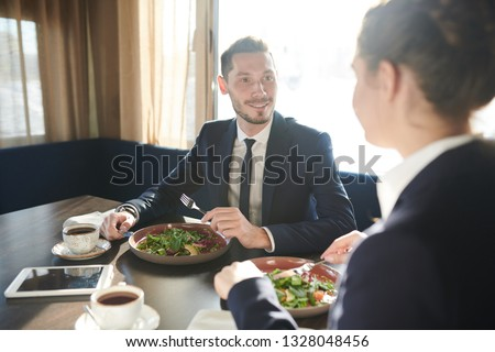 Young elegant businessman eating fresh vegetable salad at lunch break with his colleague or partner in front