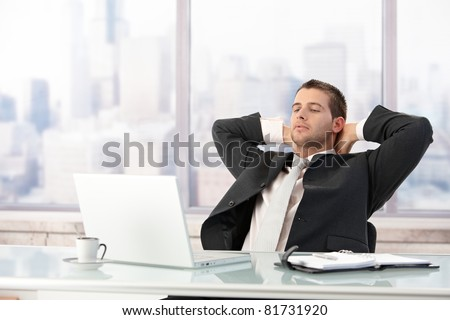 Young elegant businessman stretching on chair in office.?
