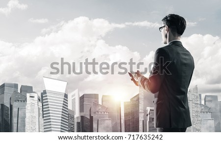 Young elegant businessman with diary in hands looking away #717635242