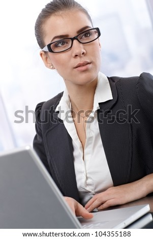 Young elegant businesswoman wearing glasses, working on laptop computer.