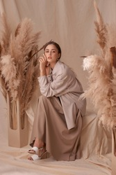 Young elegant female model sitting at beige textile background and posing between ears of rye. Brunette girl with makeup and pony tail hair in white shirt and beige skirt and jacket