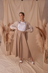 Young elegant female model standing on beige textile background and posing between ears of rye. Brunette girl with makeup and pony tail hair in white shirt and beige skirt and jacket