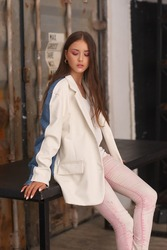 Young elegant girl in stylish pink jeans, white shirt and white and blue blazer sitting at table. Fashion portrait. Pretty woman with long straight brunette hair