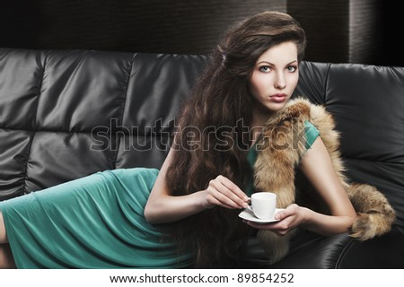 young elegant lady laying down on sofa keeping and drinking from a little cup of coffee. wearing green dress.she is lying on the sofa and takes the cup with both hands.