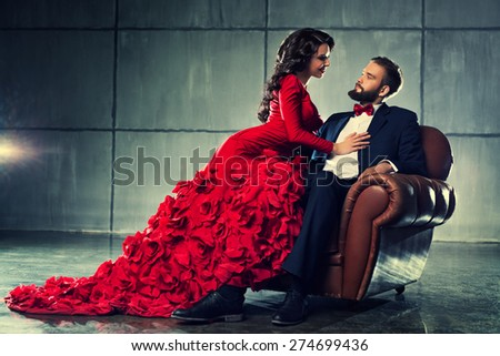 Young elegant loving couple in evening dress portrait. Woman in red and man in black suit sitting on chair.