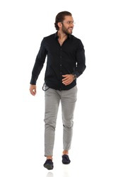 Young elegant man in moccasins, gray trusers, and black shirt is walking towards camera, looking away and smiling. Full length studio shot isolated on white.