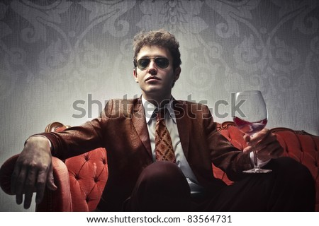 Young elegant man sitting on a velvet sofa and holding a glass of wine - stock photo