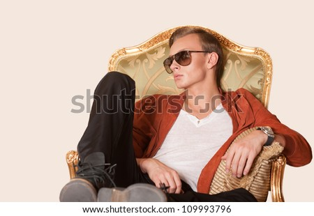 Young elegant man sitting on armchair. Isolated.