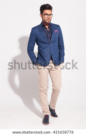 young elegant model wearing suit in walking pose looking away from the camera in studio