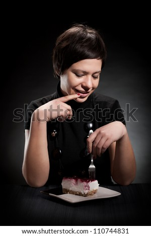 Young elegant woman eating a chocolate cake