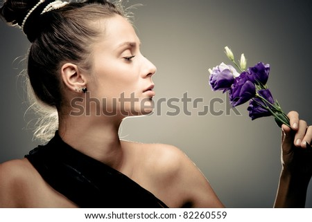 young elegant woman hold flowers, profile, studio shot