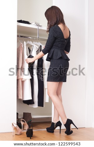 young elegant woman in front of open closet full of elegant dresses choose what to wear full body shot