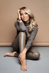 Young elegant woman in gray pullover and leather skinny leggings posing in studio. Beautiful fashion lady with wavy healthy blond hair, daily makeup sit barefoot on floor over beige wall background