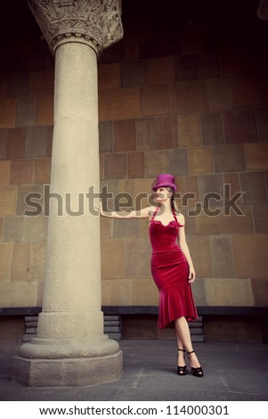 young elegant woman in red dress and cylinder  leaning against column, full body shot