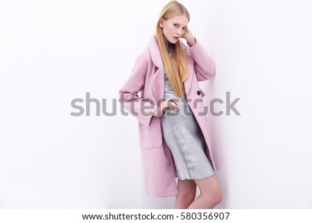 Young elegant woman in trendy pink coat. Blond hair, silver dress, isolated studio shot.