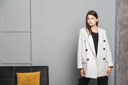 Young elegant woman in white oversize blazer and black ripped pants. Interior portrait