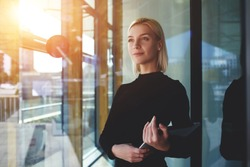 Young elegant woman thinking something while standing with touch pad near office window outside, female employer holding digital tablet while looking forward to meeting with international partners