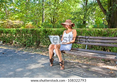 Young elegant woman with hat in white dress sitting on bench in park and working on laptop - stock photo