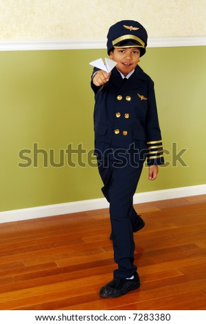 Young elementary boy in an airline pilot's uniform flying a paper airplane