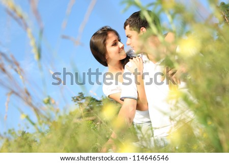 Young embracing couple enjoying the spring in meadow