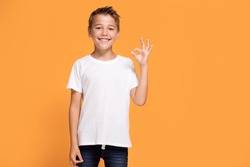 Young emotional handsome boy standing on orange studio background. Human emotions, facial expression concept.