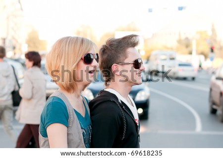 Young emotional happy teenage couple walking in city street