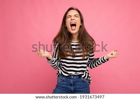 Young emotional positive happy attractive brunet woman with sincere emotions in casual striped pullover isolated on pink background with free space and celebrating victory shouting yes Foto stock ©