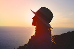 Young emotional woman enjoying sunset on cliff silhouette