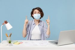 Young employee business woman in shirt face mask ppe from coronavirus covid-19 on lockdown quarantine sit work at office desk with pc laptop point finger overhead on area isolated on blue background