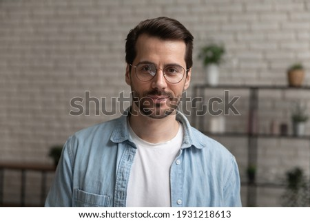 Young employee. Headshot portrait of confident millennial male wearing glasses posing indoors. Professional speaker coach tutor look at camera give remote business consultation present idea on webinar